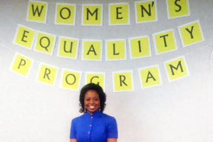 Dr. Shirley Davis standing under a Women's Day Sign